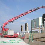 kranbil heiser prefabrikerte hus på lasteplanet