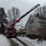 kranbil heiser takstein opp på taket