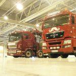 kranbiler oppstilt på rekke inne i en hall